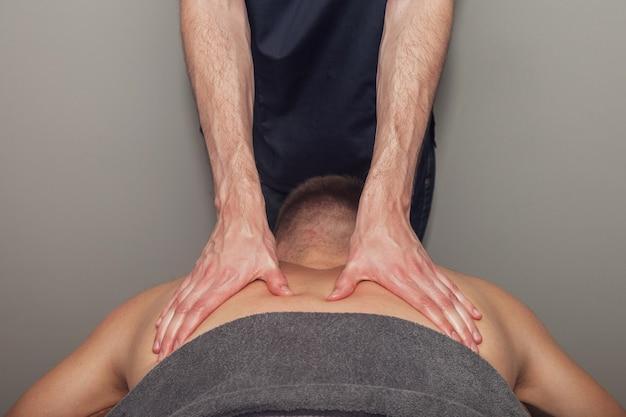 L'uomo dei giovani atleti gode del massaggio benessere sportivo nell'ufficio medico della sala fitness