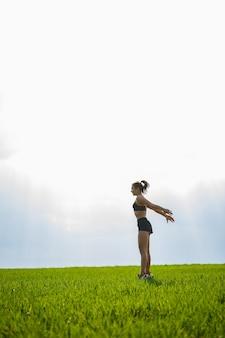 La giovane ragazza atletica fa saltare sull'erba prima del tramonto. esercizio, sport, stile di vita sano