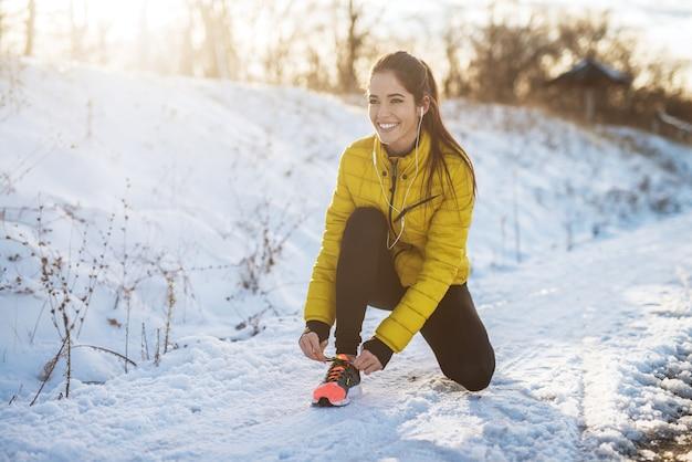 Giovane ragazza atletica che lega i laccetti in abiti sportivi di inverno sulla strada nevosa di inverno con le cuffie nella mattina soleggiata.