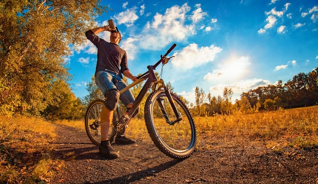 Il giovane ragazzo atletico in una maglietta nera e un berretto da baseball su una bici sportiva beve l'acqua da uno shaker nel paesaggio di autunno
