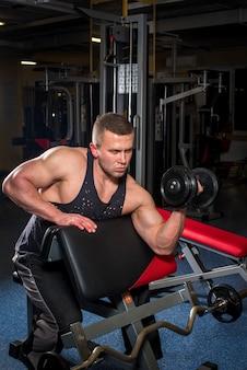 Un giovane ragazzo atletico è impegnato in palestra in palestra. fitness, bodybuilding.