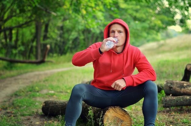 Un giovane jogger atletico in una giacca rossa con cappuccio e leggings neri si siede su un tronco e beve acqua da una bottiglia dopo aver corso su una foresta verde primaverile.