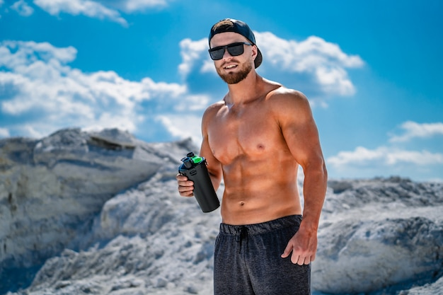 Acqua potabile del giovane uomo atletico o frullato di proteine dopo l'allenamento. recupero dopo allenamento.
