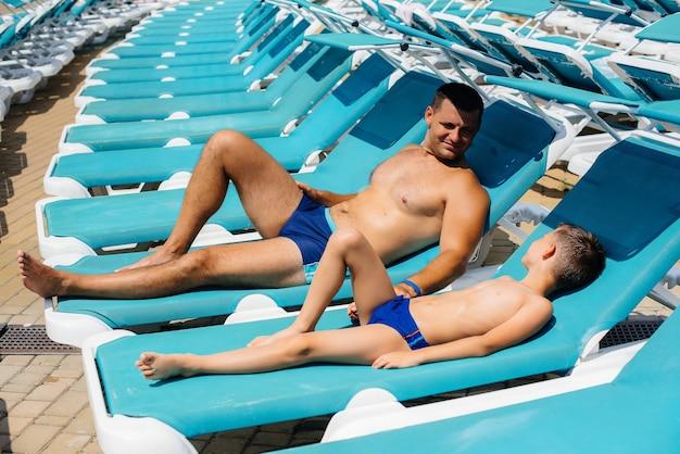 Un giovane uomo atletico e suo figlio sorridono felici e prendono il sole su un lettino in una giornata di sole. buone vacanze. vacanze estive e turismo.