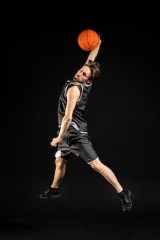 Giovane uomo atletico che tiene un pallone da basket