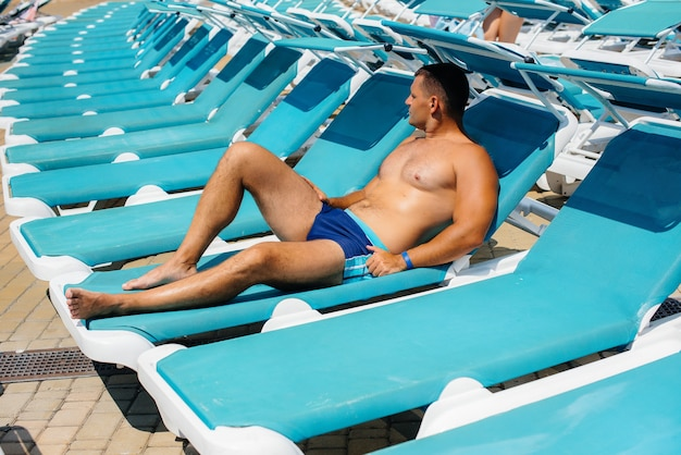 Un giovane uomo atletico sorride felicemente e prende il sole su un lettino in una giornata di sole. buone vacanze. vacanze estive e turismo.