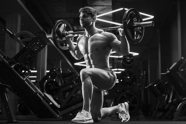 Giovane uomo atletico che pompa i muscoli in palestra durante l'allenamento sport e concetto di assistenza sanitaria