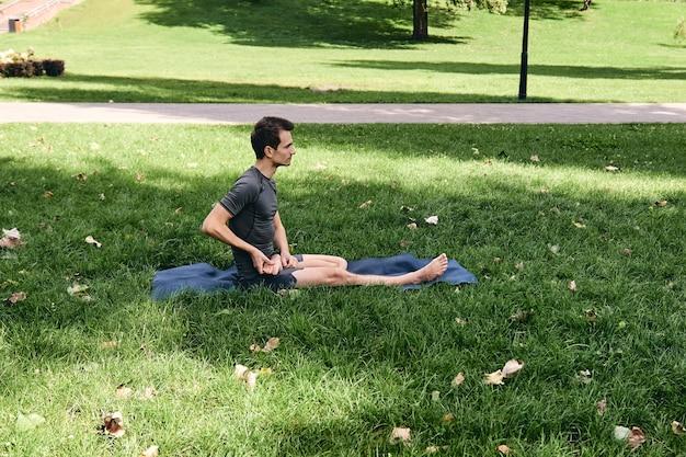 Giovane uomo atletico in abiti sportivi che fa yoga nel parco. pratica le asana all'aperto. persone che si esercitano sull'erba verde con materassino yoga. fitness e stile di vita sano. concetto di calma e meditazione
