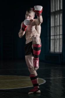Giovane uomo atletico con guantoni da boxe e una cremagliera