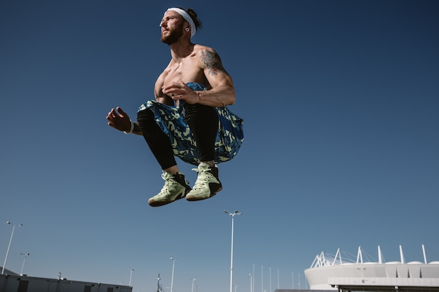 Giovane uomo atletico con un torso nudo con fascia vestita con leggings neri e pantaloncini blu sta saltando in alto sullo sfondo del cielo blu in una calda giornata di sole.