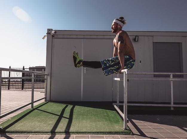 Giovane uomo atletico con un torso nudo con tatuaggi e con fascia vestita con leggings neri e pantaloncini blu sta facendo esercizi sportivi su recinzioni metalliche in una calda giornata di sole.