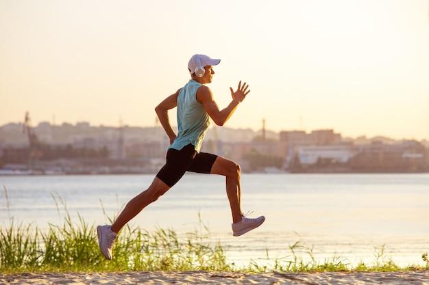 Giovane uomo atletico che si allena, si allena in riva al fiume all'aperto.