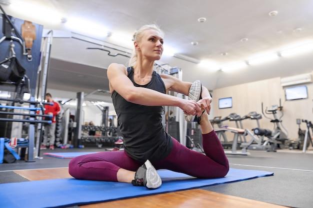Giovane donna muscolare atletica che fa allungando allenamento in palestra