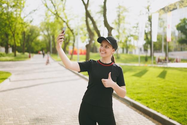 Giovane atletica sorridente bella ragazza bruna in uniforme nera, berretto facendo selfie sul telefono cellulare durante l'allenamento, mostrando pollice in su, in piedi nel parco cittadino all'aperto