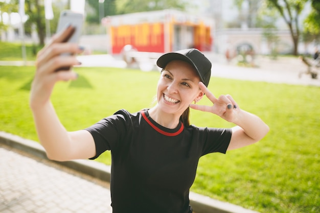 Giovane atletica sorridente bella ragazza bruna in uniforme nera e berretto facendo selfie sul telefono cellulare durante l'allenamento, mostrando il segno della vittoria, in piedi nel parco cittadino all'aperto