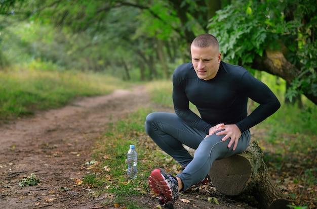 Un giovane sportivo atletico in camicia nera, leggings e scarpe da ginnastica si siede su un tronco, soffre e tiene con la mano un'anca con le mani dopo i crampi in una foresta verde primaverile.