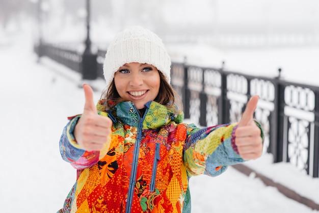 Una giovane donna atletica fa sport in una giornata gelida e nevosa e mostra i pollici in su. fitness, corsa