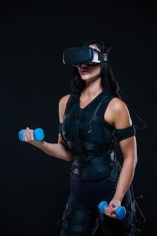 Una giovane donna atletica in una tuta ems e occhiali per realtà virtuale con manubri