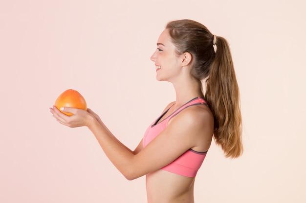 Giovane donna atletica nel profilo con un pompelmo in sue mani.