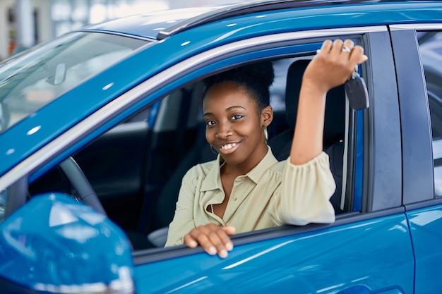 La giovane donna afro attraente ama essere proprietaria di una nuova auto