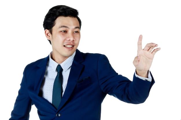 Giovane uomo d'affari asiatico attraente che indossa un abito blu navy con camicia bianca e cravatta sorridente e, mettendo le mani fuori per raggiungere qualcosa. sfondo bianco. isolato
