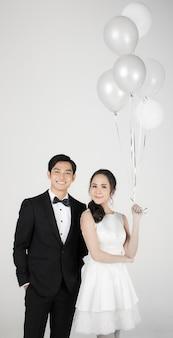 Giovane coppia asiatica attraente, sposa e sposo, donna che indossa abito da sposa bianco con palloncino. uomo che indossa uno smoking nero, in piedi insieme. concetto per la fotografia prematrimoniale.