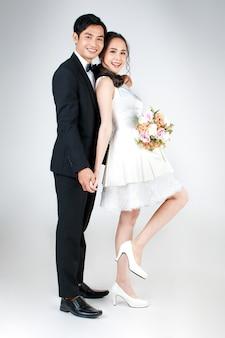 Giovane coppia asiatica attraente, sposa e sposo, donna che indossa abito da sposa bianco che tiene un mazzo di fiori. uomo che indossa uno smoking nero, in piedi insieme. concetto per la fotografia prematrimoniale.