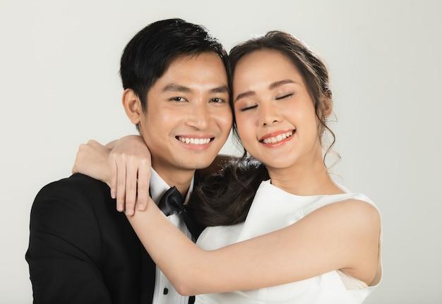 Giovane coppia asiatica attraente, sposa e sposo, donna che indossa abito da sposa bianco. uomo che indossa uno smoking nero, abbracciati. concetto per la fotografia prematrimoniale.