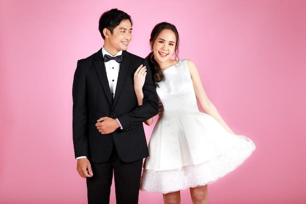 Giovane coppia asiatica attraente, sposa e sposo, donna che indossa abito da sposa bianco. uomo che indossa uno smoking nero, in piedi a braccetto insieme su sfondo rosa. concetto per la fotografia prematrimoniale.