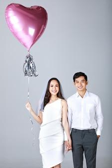 Giovane coppia asiatica attraente, uomo che indossa una camicia bianca, donna che indossa un abito bianco con velo da sposa in piedi insieme tenendosi per mano. pallone della holding della donna. concetto per la fotografia prematrimoniale.