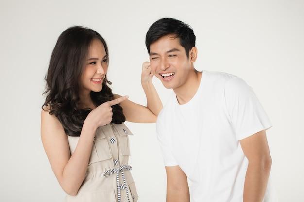 Giovane coppia asiatica attraente, uomo che indossa maglietta bianca e pantaloni beige, donna che indossa abito beige. prendere in giro l'un l'altro. concetto per la fotografia prematrimoniale.