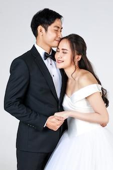 Giovane coppia asiatica attraente, presto sposa e sposo, donna che indossa abito da sposa bianco. uomo che indossa uno smoking nero, abbracciati. concetto per la fotografia prematrimoniale.
