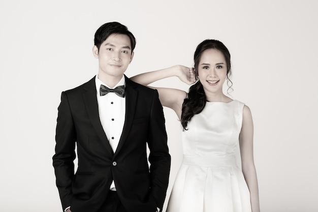 Giovane coppia asiatica attraente, presto sposa e sposo, donna che indossa abito da sposa bianco. uomo che indossa uno smoking nero, in piedi insieme. concetto per la fotografia prematrimoniale.