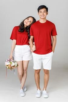 Giovane coppia asiatica attraente che indossa maglietta rossa e pantaloncini bianchi in piedi insieme, donna che tiene un mazzo di fiori su sfondo bianco. concetto per la fotografia prematrimoniale. isolato.
