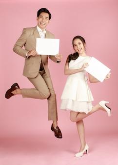 Giovane attraente coppia asiatica donna che indossa abito da sposa bianco, uomo che indossa un abito beige con cartelli che saltano insieme su sfondo rosa. concetto per la fotografia prematrimoniale.