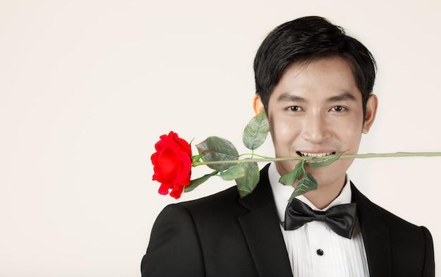 Giovane uomo asiatico attraente, presto sposo che indossa uno smoking nero che tiene una rosa rossa con i denti. concetto per la fotografia prematrimoniale.