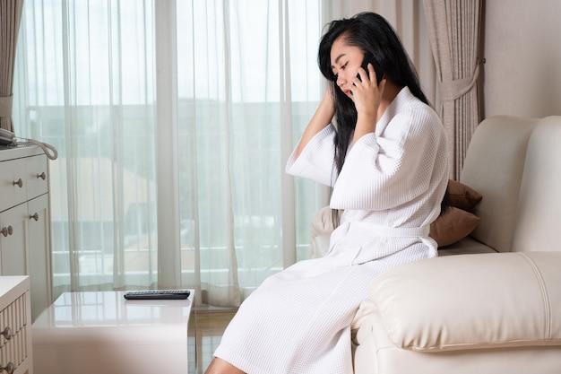 Giovane donna asiatica attraente in accappatoio seduta sul divano che parla al telefono in camera