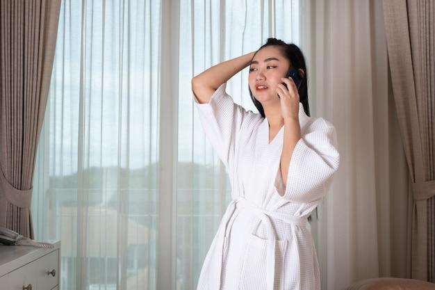 Giovane donna asiatica attraente in accappatoio in piedi e parlando al telefono in soggiorno