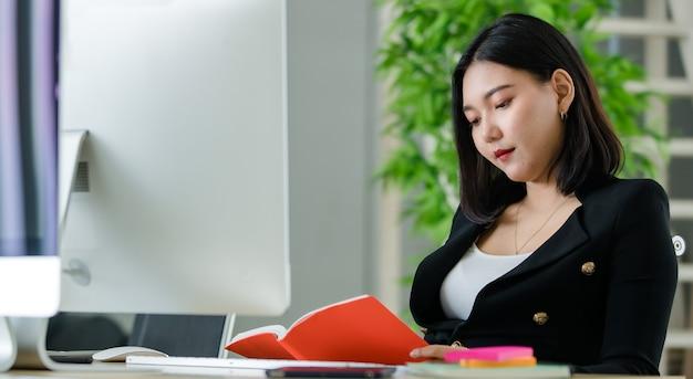 Giovane donna asiatica attraente in tailleur nero seduto in un ufficio moderno che legge un libro con copertina rossa. concetto per lo stile di vita moderno dell'ufficio.