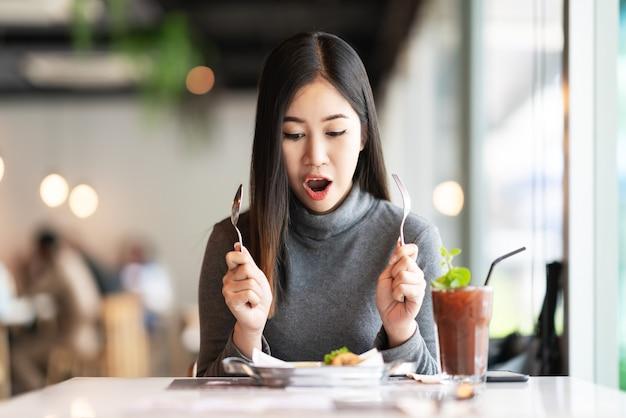 Giovane sensibilità asiatica attraente della forchetta e del cucchiaio della tenuta della donna affamata