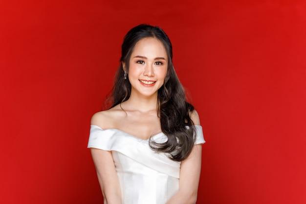 Giovane donna asiatica attraente che presto sarà sposa indossando un abito da sposa bianco che tiene in mano un mazzo di fiori su sfondo rosso. concetto per la fotografia prematrimoniale.