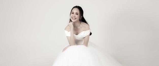 Giovane donna asiatica attraente, presto sposa, con indosso un abito da sposa bianco seduto con aria felice. concetto per la fotografia prematrimoniale. in seppia