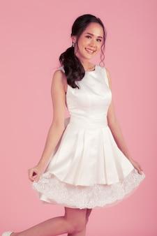 Giovane donna asiatica attraente che indossa abito da sposa bianco su sfondo rosa. concetto per la fotografia prematrimoniale.