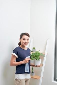 Giovane donna asiatica attraente che dà acqua a una pianta