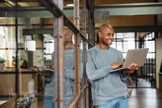 Giovane attraente calvo americano africano uomo che indossa una felpa tenendo il computer portatile mentre si lavora in office