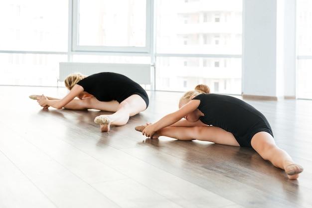Giovane insegnante di balletto attraente e il suo piccolo studente facendo esercizi sul pavimento in studio