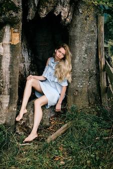 Giovane ragazza bionda a piedi nudi attraente in vestito blu che si siede nel vecchio albero