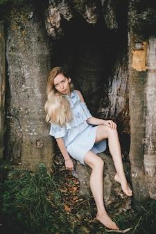 Giovane ragazza bionda a piedi nudi attraente in vestito romantico blu che si siede nel vecchio albero
