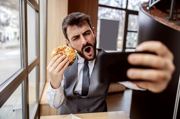 Giovane uomo d'affari barbuto attraente seduto in un ristorante fast food, tenendo delizioso hamburger al formaggio e prendendo selfie.