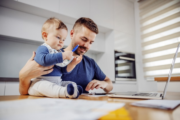 Giovane padre barbuto attraente seduto al tavolo da pranzo con il suo amato figlio adorabile e pagare le bollette online. il suo ragazzo che tiene la penna e cerca di aiutarlo.
